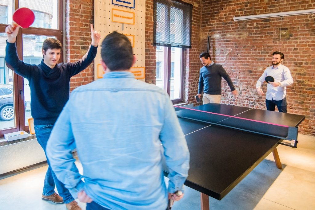 colleagues play ping pong